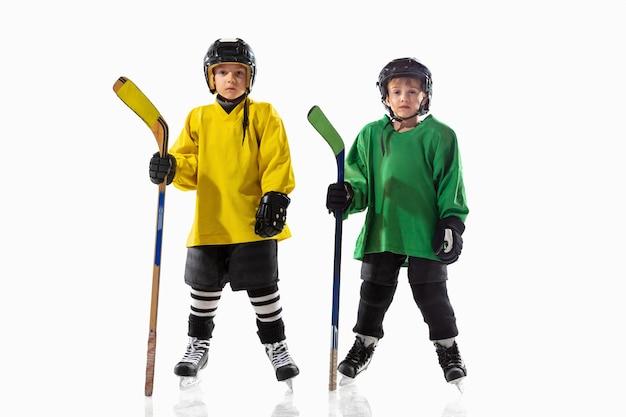 Petits joueurs de hockey avec des bâtons sur un court de glace et un mur blanc. sportsboys portant des équipements et un casque pratiquant. concept de sport, mode de vie sain, mouvement, mouvement, action.