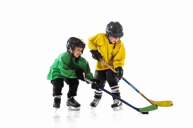 Petits joueurs de hockey avec les bâtons sur un court de glace et un mur de studio blanc