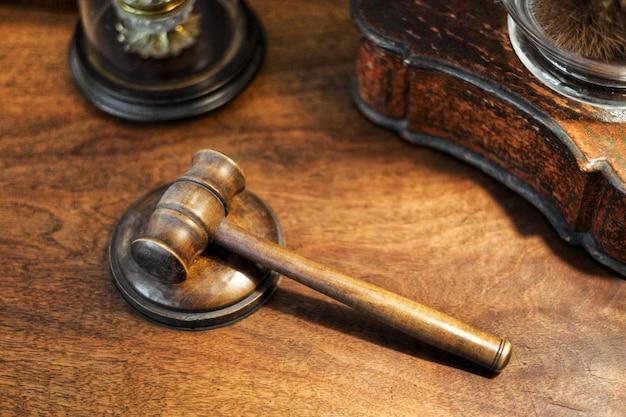 Petits juges en bois marteau sur un bureau dans un grand angle de vue conceptuel du crime, de l'ordre public, de la détermination de la peine, d'un tribunal ou d'une vente aux enchères