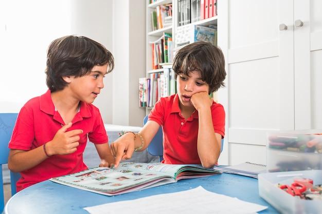 Petits jumeaux discutant livre