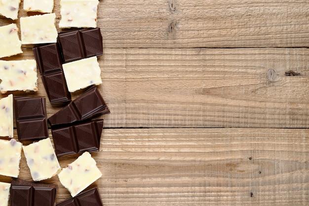 Petits morceaux de chocolat sur fond en bois