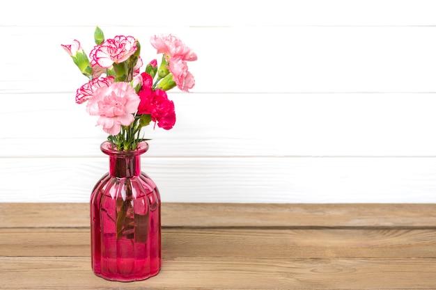 Petits oeillets roses colorés dans un vase sur fond de bois et mur blanc