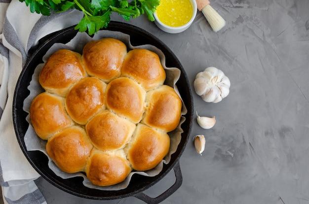 Petits pains à l'ail ukrainiens traditionnels dans une poêle en fonte sur un fond de béton foncé.