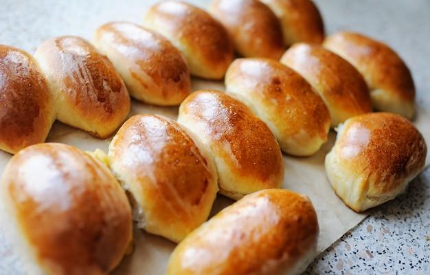 Petits pains appétissants avec un gros plan de croûte dorée sur une surface claire. gateau maison