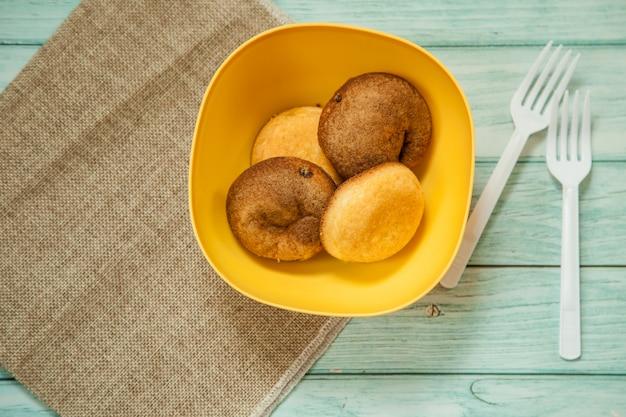 Petits pains au four sur un bol en bois sur un sac avec des fourchettes blanches