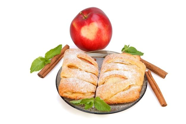 Petits pains aux pommes, cannelle et menthe saupoudrés de sucre en poudre sur une assiette et pomme rouge avec coeur sur blanc