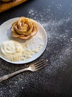 Petits pains aux pommes roses servis avec crème fouettée et pétales d'amandes