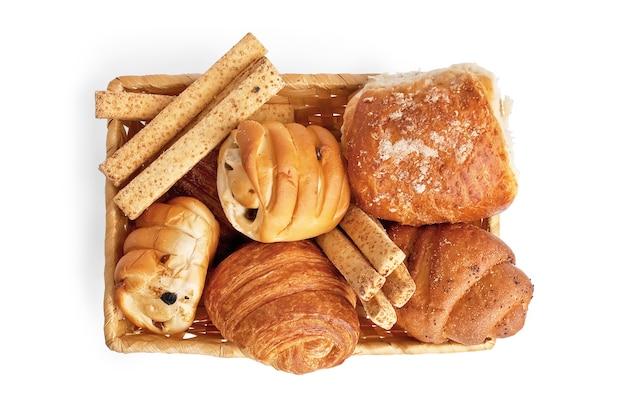 Petits pains aux raisins secs, bâtonnets de pain, croissants, petit pain feuilleté avec du gravier dans un panier en osier isolé sur fond blanc