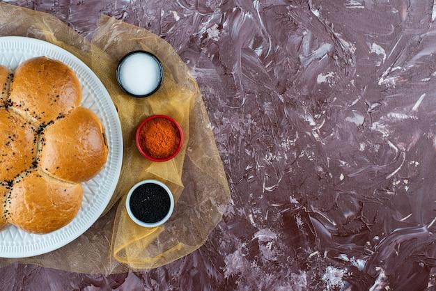 Petits pains blancs frais avec du sel et du poivre sur un fond clair.