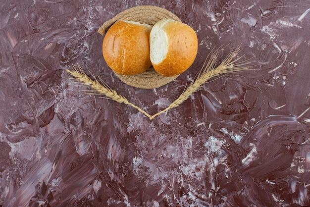 Petits pains blancs frais avec des épis de blé sur fond clair.