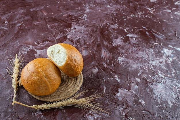 Petits pains blancs frais avec des épis de blé sur une surface légère