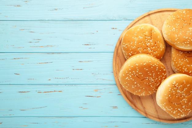 Petits pains burger sur une planche à découper sur un fond en bois bleu. vue de dessus.