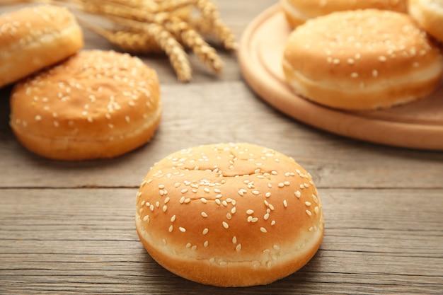 Petits pains burger sur une planche à découper sur un fond en bois gris. vue de dessus.