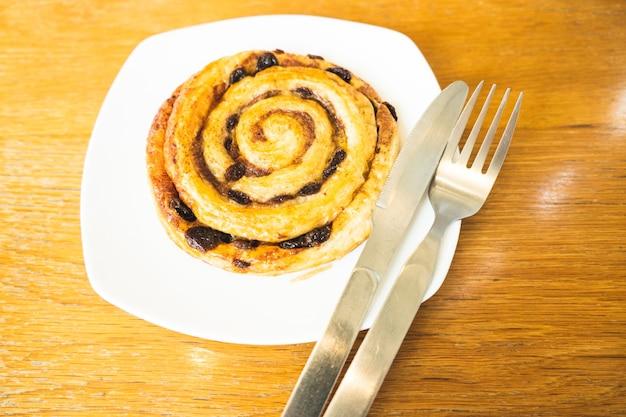 Petits pains à la cannelle cuisson sur une table de petit-déjeuner plaque blanche vue de dessus.