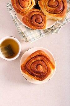 Petits pains à la cannelle fraîchement sortis du four servis avec du thé