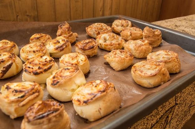 Des petits pains à la cannelle maison fraîchement cuits se trouvent sur une plaque à pâtisserie