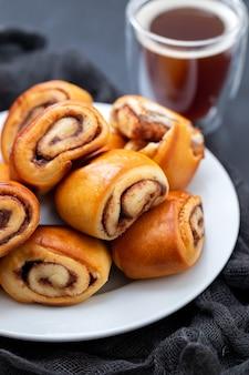 Petits pains à la cannelle sur plaque blanche et tasse de café sur table en céramique