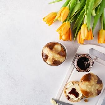 Petits pains chauds, beurre et confiture pour le petit-déjeuner de pâques et tulipes
