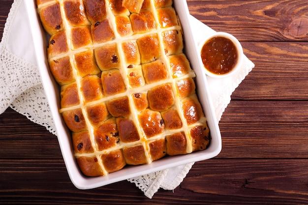 Petits pains chauds fraîchement cuits dans une boîte, glacés avec de la confiture