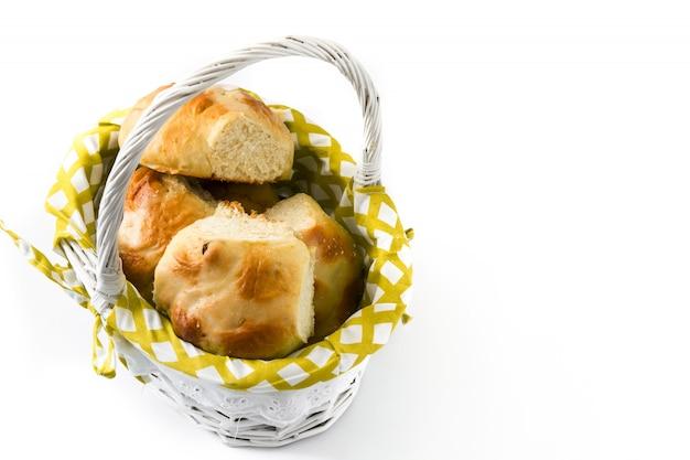 Petits pains chauds traditionnels de pâques dans un panier sur blanc