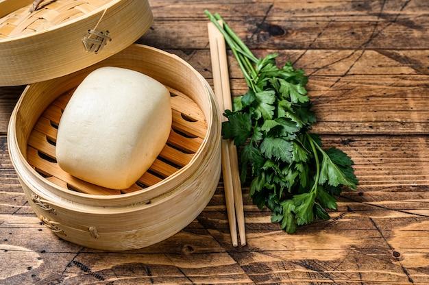 Petits pains chinois cuits à la vapeur dans un cuiseur vapeur traditionnel en bambou. fond en bois. vue de dessus. espace de copie.