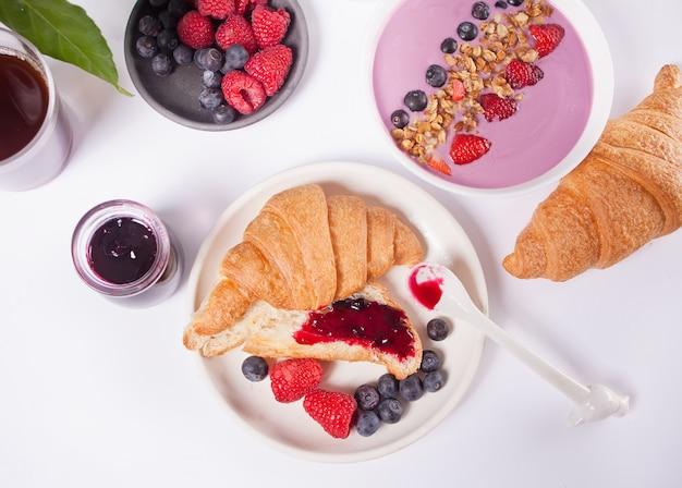 Petits pains croissants frais, baies, confiture de cassis. concept de petit déjeuner.