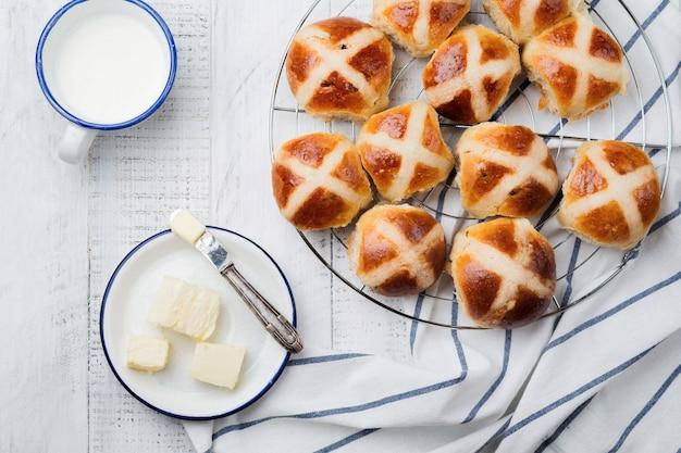 Petits pains de croix chaude de pâques faits maison sur un plateau en bois avec du textile en lin et des branches de saule sur fond de bois blanc. mise au point sélective. vue de dessus. copiez l'espace.