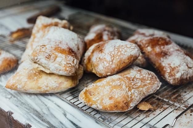 Des petits pains cuits au four fraîchement et chauds sont placés sur le comptoir en marbre pour la vente. fait maison par artis