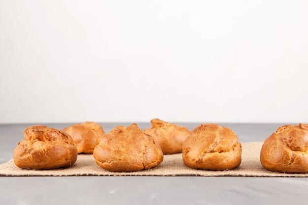 Petits pains dorés frais de la pâte à la crème (profiteroles) sur une table lumineuse