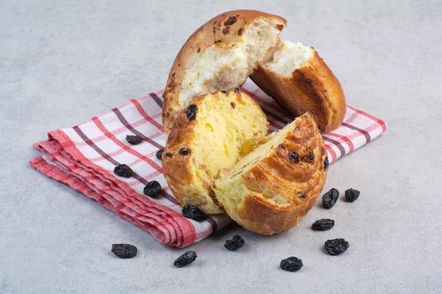 Petits pains faits maison aux raisins secs et fromage sur nappe. photo de haute qualité