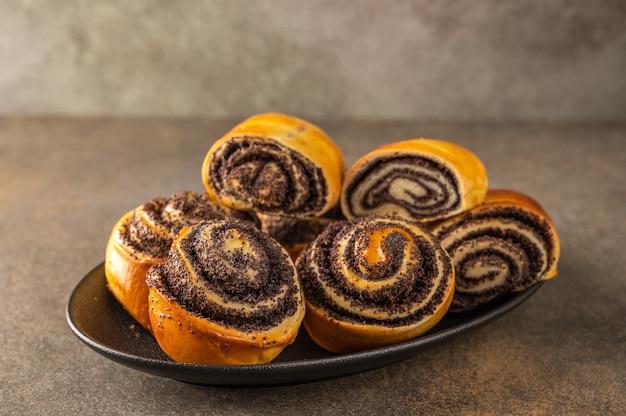 Petits pains faits maison avec des graines de pavot sur une plaque blanche sur un fond sombre close-up.