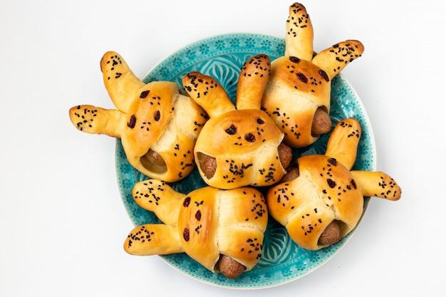 Petits pains en forme de lièvre avec des saucisses pour enfants situés sur une plaque bleue sur fond blanc, une idée culinaire pour les enfants