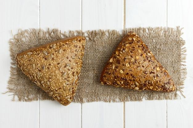 Petits pains fraîchement cuits au four avec des graines sur une table en bois