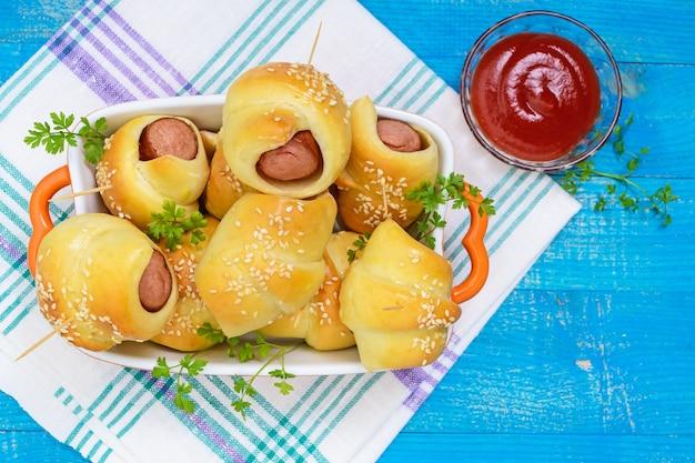 Petits pains fraîchement cuits dans un bol en céramique. saucisse dans la pâte