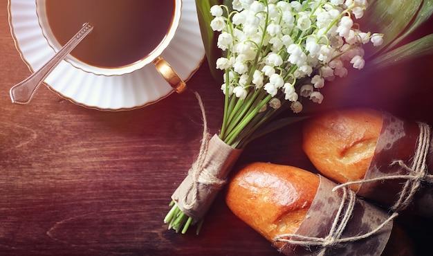 Petits pains frais pour le petit déjeuner. bun avec du beurre à une tasse de café le matin. petit déjeuner à l'hôtel brioches confiture thé et bouquet de fleurs.