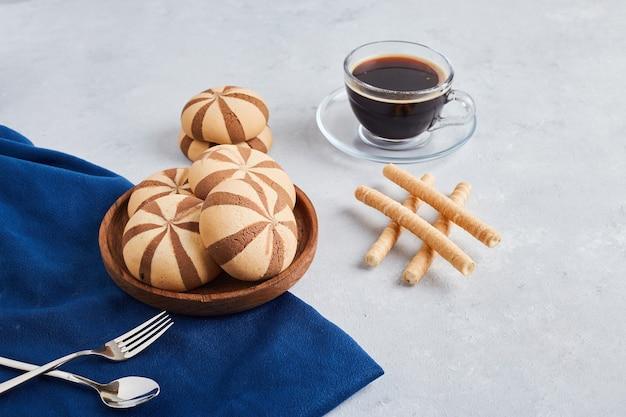 Petits pains et gaufres au cacao avec une tasse de café sur une nappe bleue.
