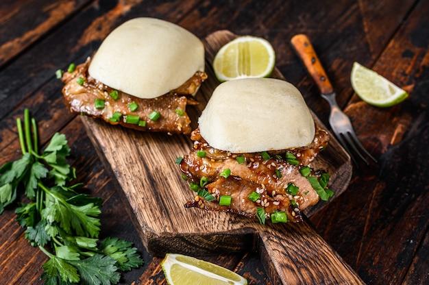 Petits pains gua bao cuits à la vapeur de sandwich chinois avec du porc. fond noir. vue de dessus.