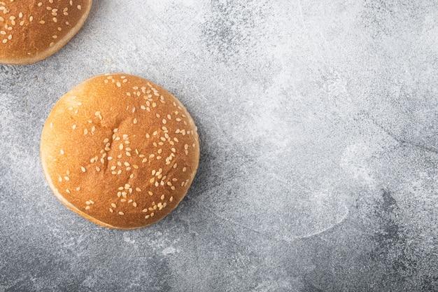 Petits pains à hamburger au sésame, sur table grise, vue de dessus à plat