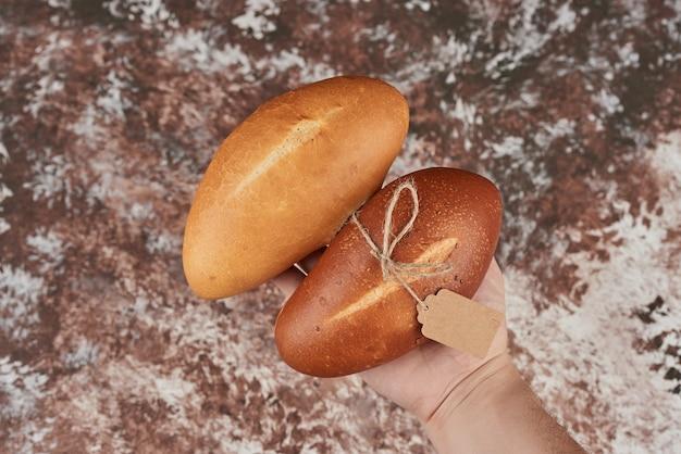 Petits pains isolés sur marbre dans la main.