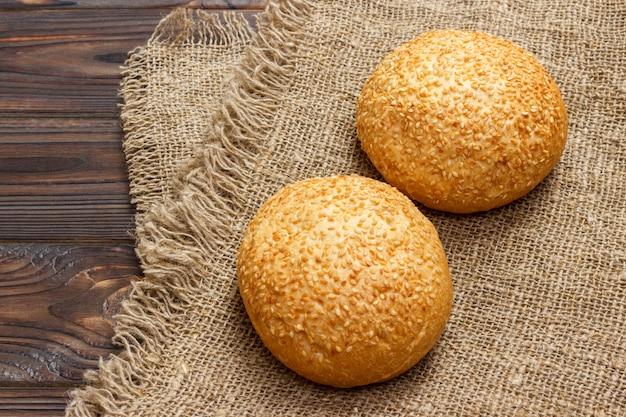 Petits pains maison aux graines de sésame sur une table en bois