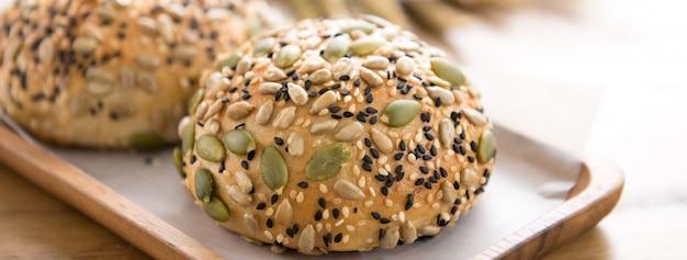 Petits pains multigrains cuits au four en bonne santé, servis sur une plaque de bois dans une boulangerie