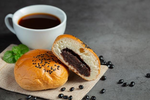Petits pains en pâte de haricots noirs cuits au four sur tissu marron, servis avec du café