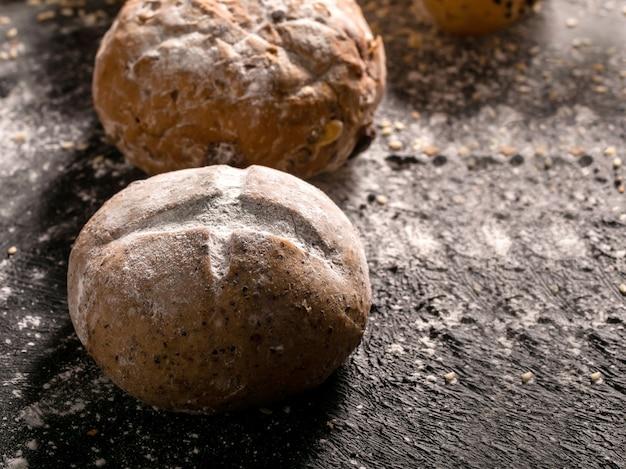 Petits pains placés sur fond de bois noir