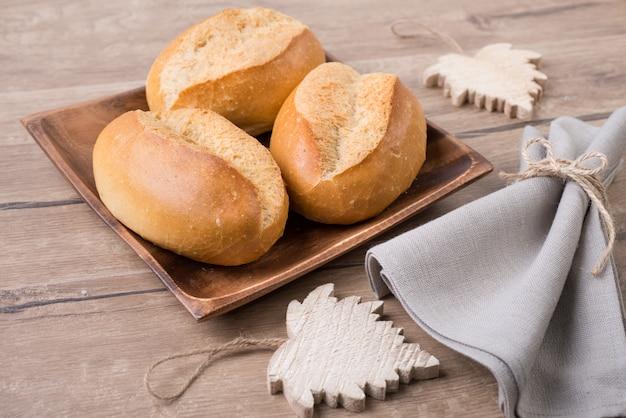 Petits pains sur plaque en bois avec serviette en lin et feuilles de bois
