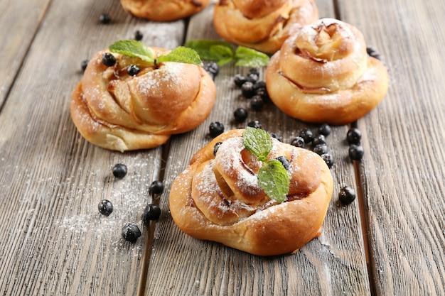 Petits pains savoureux aux baies sur table close-up