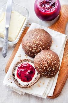 Petits pains de seigle faits maison avec graines de lin, sésame et pavot blanc servis avec beurre et confiture