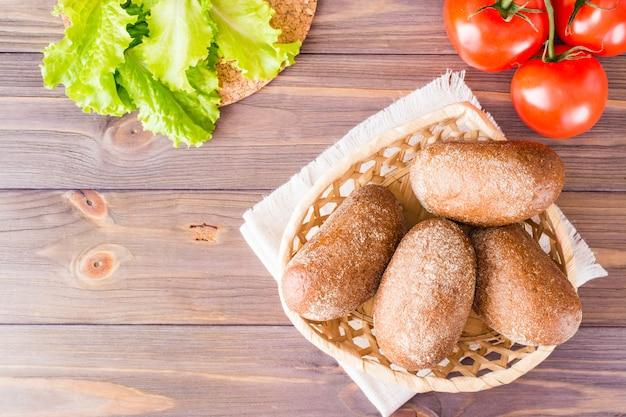 Petits pains de seigle frais dans un panier, salade et tomates sur une table en bois