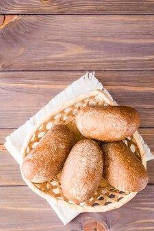 Petits pains de seigle frais dans un panier sur une table en bois