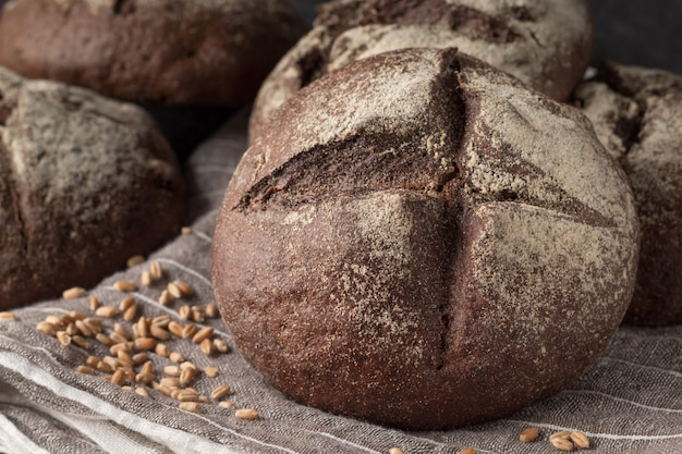 Petits pains de seigle savoureux sur tissu gris, gros plan