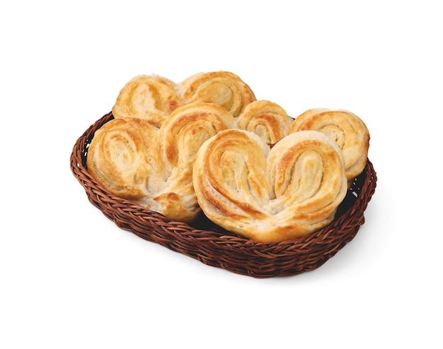 Des petits pains sucrés en forme de cœur avec du sucre se trouvent dans un panier en osier et sont isolés sur un fond blanc propre avec de petites ombres douces.